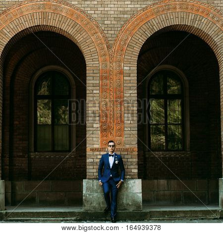 Handsome groom stands next to the arch