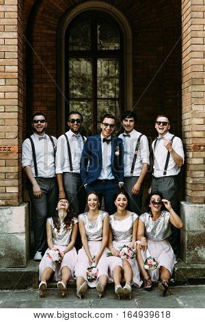 Groomsmen with a groom and bridesmaids in the arch