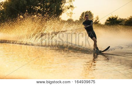 Man riding wakeboard in a lake. Water skier in action on the lake