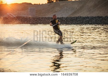 Outdoor shot of man wakeboarding on lake. Water skiing on lake behind a boat.