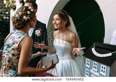 Joyful Married Couple Is Listening Greetings Of Guests