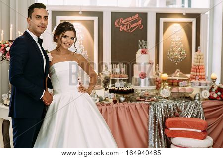 Beautiful Couple And Wedding Table With Sweets