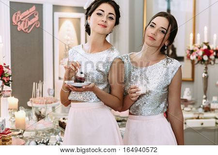 Pretty bridesmaids are eating cake desserts in the room