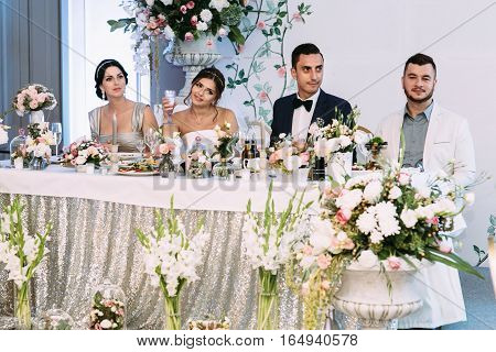 Bride is holding a glass of champagne next to the groom