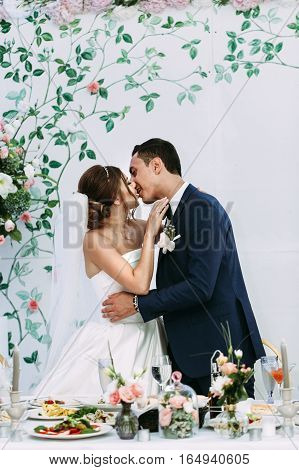 Romantic Kiss Of The Married Couple Next To The Table