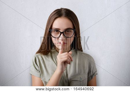 A photo of serious attractive girl with dark straight hair and confident face wearing glasses putting her finger on the mouth standing over grey background. A sign of secrecy. A gesture of silence.