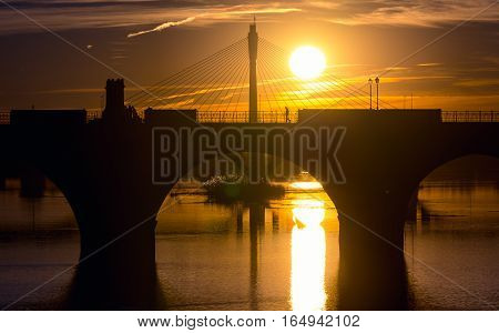 backlighting palms bridge and Guadianas River in sunlate