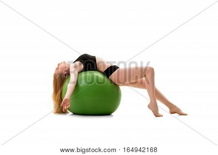 Long haired blonde in black shorts and briefs lying on her back on green big fitball posing in studio