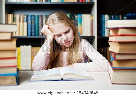 Angry And Tired Schoolgirl Studying With A Pile Of Books