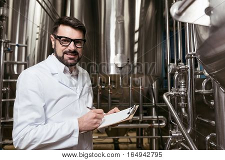 Feel responsible. Hardworking handsome young man making notes while working at beer factory and using the mechanism.