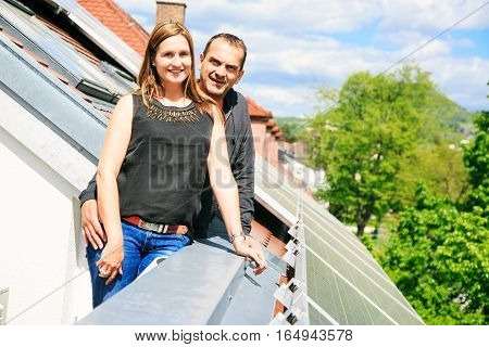 these home owners are happy with the solar panels on their roof. they save a lot of money by generating their own electricity.