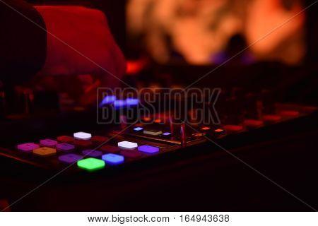 Disc jockey interacting with mixer in a nightclub