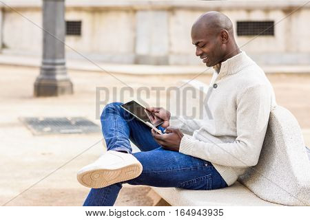 Black Young Man Looking At Tablet Computer And Smartphone