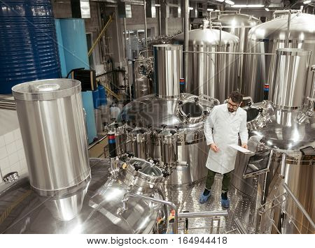 High responsibility. Responsible handsome young man standing in machinery at beer factory while working and making important notes.