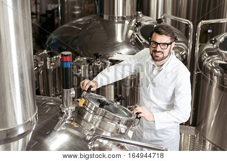 Modern technologies. Smiling young handsome man using mechanism at beer factory while working and controlling the process.