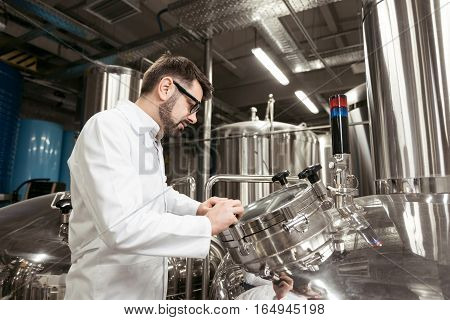 Difficult to use. Concentrated young handsome man looking at brewing mechanism at beer factory while working and controlling the process.