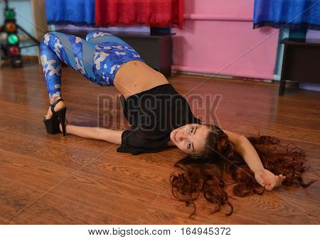 Sexy young woman GO-GO dancer posing lying on the floor.
