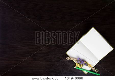 Open notebook with boutonniere and green pencil in the corner of dark wooden background. Top view. Flat lay. Can be used as a field for notes, notebook cover.