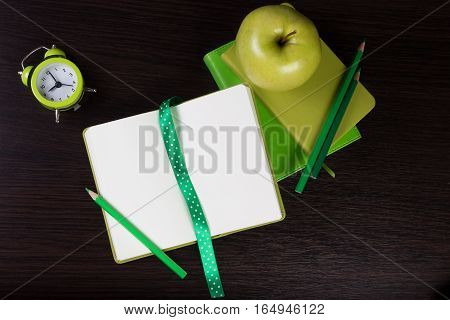 Open notebook, pencils clock and apple on dark wooden background. Different tints of green. Top view. Flat lay. Can be used as a field for text, notebook cover.
