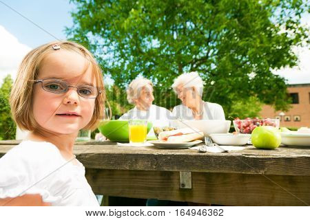 little girl and her grandparents are sitting at a picnic table