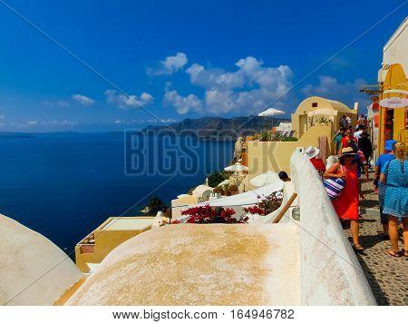 Oia Greece - June 10 2015: Santorini - The people going at beautiful terrace with sea view on Santorini island Oia Greece on June 10 2015.