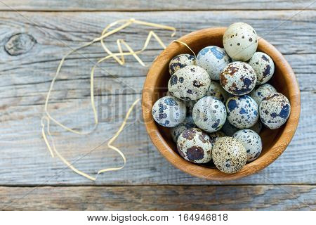 Colorful Quail Eggs In A Wooden Bowl.