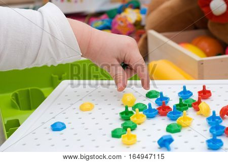 Baby with multicolour mosaic toy on the floor