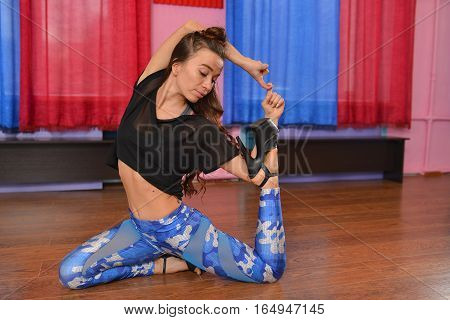 Portrait of beautiful young woman dancer working out in studio. Fit sporty girl stretching