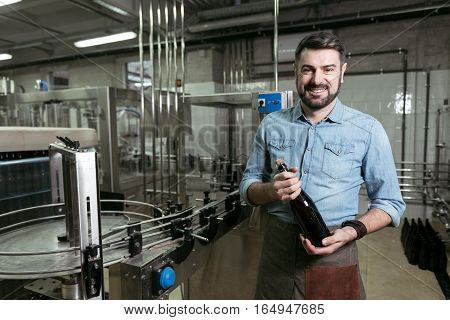 Happy workday. Smiling handsome young man holding a bottle of alcohol while working at brewing factory and posing.