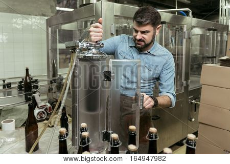 Doing it to death. Concentrated young handsome man working hard while spending time in brewery and making alcohol.
