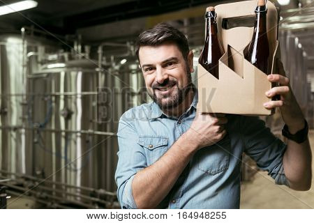 Joyful brewer. Overjoyed young handsome man holding bottles of alcohol while standing in brewery and smiling.