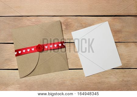 Envelope with red ribbon and a piece of paper on wood background