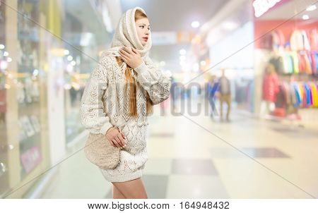 Young smiling beautiful stylish blonde woman in white knitted scarf with fringe and long patterned sweater with crocheted bag in hands walks in shopping centre.