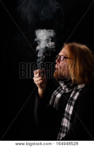 Beautiful stylish thoughtful long-haired man with red beard in chequered scarf and glasses holds tobacco pipe and puffs smoke isolated on black background