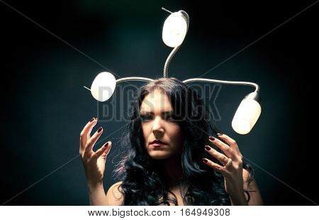 young woman with snakelike lamps behind her head. really scary.