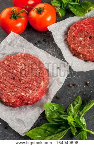 Fresh raw home-made minced beef steak burger with spices basil and tomatoes on a cutting board on a stone table copy space top view
