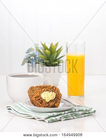Fresh bran muffin served with coffee and orange juice.