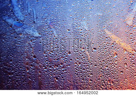 Closeup of condensation patterns on glass window, Rain droplets with light shining through, detail reflection / refraction