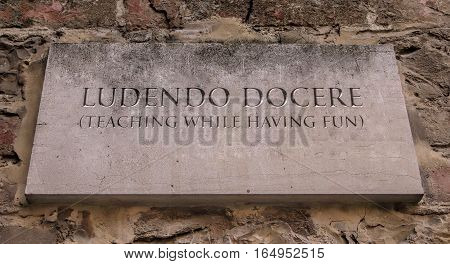 Ludendo docere. Latin phrase, usually translated into English as Teaching while having fun.