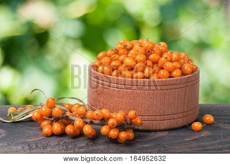 Sea-buckthorn berries in a wooden bowl on a table with blurred garden background.