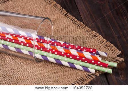 Colorful drinking striped straws in glass on a wooden table with sacking.