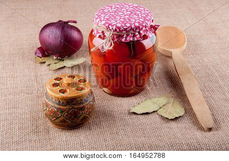 Composition of products and tableware lay on sackcloth. Red onion bay leaves tomatoes in transparent glass jar covered by cloth wooden spoon and round box with pattern.