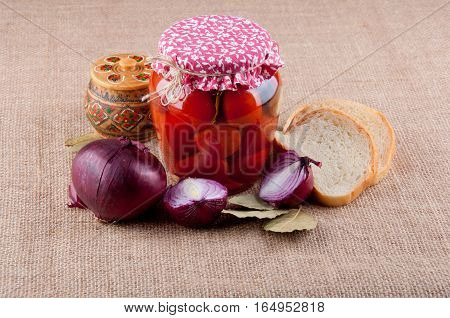 Wooden box with pattern for salt red onion bay leaves tomatoes in glass jar pieces of white bread lay on brown sackcloth