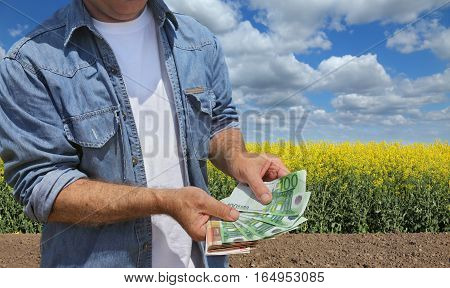 Farmer hold Euro banknote with blossoming cultivated canola field in background