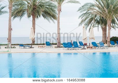 Swimming pool with stair in hotel. Summer photo concept.