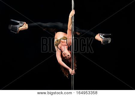 young beautiful attractive red hair woman on pylon in difficulte pose
