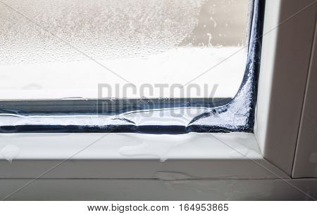 Ice inside in the corner of a window in winter. Poor warm isolation concept.