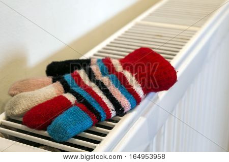 Childs knitted gloves drying on heating radiator after winter day outside