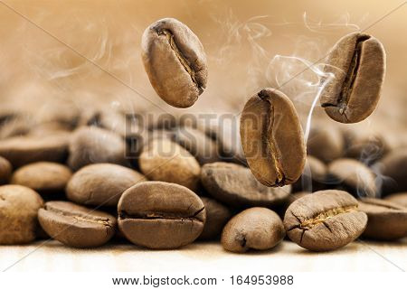 Flying fresh coffee beans as a background with copy space. Coffee beans falling down with white steam vapour.
