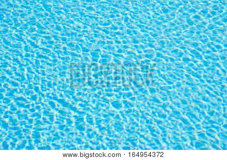 Blue ripped water in swimming pool. Pool water background. Swimming pool with stair in hotel. Summer photo concept.
